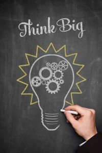 think big lightbulb written on a black chalkboard